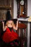 Halloween-Hexenmädchen im roten Kleid und im schwarzen Hut Lizenzfreie Stockfotografie