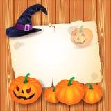 Halloween-Hintergrund mit leerem Papier, Hut und Kürbisen Lizenzfreie Stockbilder