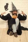 Halloween hipster with pumpkin and black cat symbol on wall. Angry man in witch hat doing magic on floor. Autumn holidays celebration. Bad luck concept. Evil stock photography