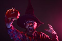 Halloween hipster in wizard hat holding pumpkin. On dark background. Mystery and magic concept. Man with scary face and jack o lantern. Autumn holiday royalty free stock photos