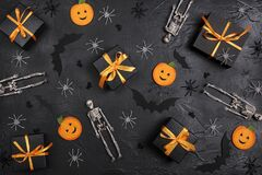 Halloween holiday background with gifts and decorations on black backdrop