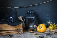 Halloween holiday background with pumpkin, lantern, spiders, old books, black witchhat stock photography
