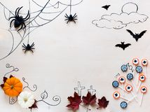Halloween holiday background with spiders, bats, candies and pumpkins on wood Stock Images