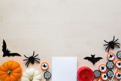 Halloween holiday background with spiders, bats, candies and pumpkins on wood Stock Photo