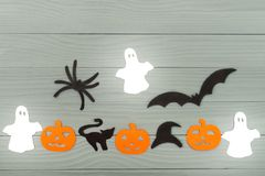 Halloween holiday background with three pumpkins, cat, spider, bats, hat and three ghosts stock photos