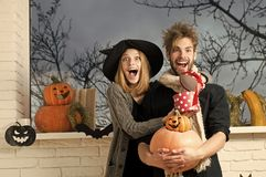 Halloween holiday celebration concept. Macho in scarf holding pumpkins. Couple in love standing surprised at window with autumn view. Presents and surprise royalty free stock image