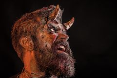Halloween holiday celebration, cosplay. Demon with bloody horns on head. Satan with beard, red blood, wounds on scary face. Hell, death, evil, horror concept stock image