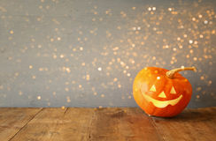 Halloween holiday concept. Cute pumpkin on wooden table. And glitter lights overlay royalty free stock photo