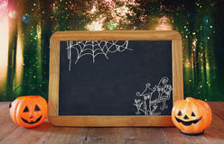 Halloween holiday concept. Cute pumpkins next to blackboard Royalty Free Stock Photos