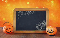 Halloween holiday concept. Cute pumpkins next to blackboard Royalty Free Stock Photo