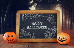Halloween holiday concept. Cute pumpkins next to blackboard Royalty Free Stock Images