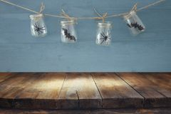 Halloween holiday concept. Empty old wooden table in front of masson jars with spiders and baths decorations Royalty Free Stock Images
