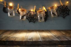 Halloween holiday concept. Empty old wooden table in front of masson jars with spiders and baths decorations Stock Images