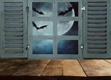 Halloween holiday concept. Empty rustic table in front of haunted night sky background and old window. Ready for product display m stock images