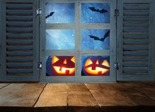 Halloween holiday concept. Empty rustic table in front of haunted night sky background and old window. Ready for product display m. Ontage royalty free stock photos