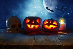 Halloween holiday concept. Empty rustic table in front of Pumpkins over wooden table at night scary, haunted and misty forest. Rea stock photo