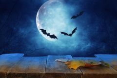 Halloween holiday concept. Empty rustic table in front of scary and misty night sky with black bats and full moon background. Read. Y for product display montage stock image