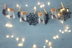 Halloween holiday concept. Masson jars with spiders, baths and wooden decorations Stock Photo