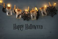 Halloween holiday concept. Masson jars with spiders, baths and wooden decorations Royalty Free Stock Photo