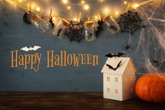 Halloween holiday concept. Mysterious house with lights in front of masson jars with spiders, baths Royalty Free Stock Photography