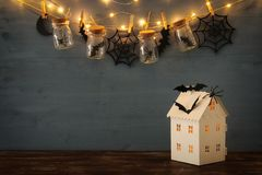 Halloween holiday concept. Mysterious house with lights in front of masson jars with spiders, baths. And wooden decorations Stock Photography