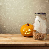 Halloween holiday decoration with ghost in jar and jack lantern pumpkin on wooden table over bokeh background Stock Photography