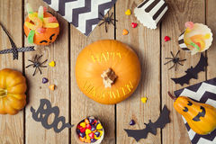 Halloween holiday decoration with pumpkin and candy on wooden table. Stock Photography