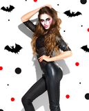 Halloween. Holiday party girl. Beautiful young woman with bright vampire makeup and long hair posing in witches costume. Halloween. Holiday party girl makeup royalty free stock images