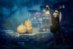 Halloween, holidays, masquerade concept - the portrait of young little beautiful girl with skull makeup on pumpkins background. Ha royalty free stock photo