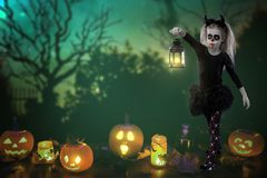 Halloween, holidays, masquerade concept - the portrait of young little beautiful girl with skull makeup on pumpkins background. Ha royalty free stock photos