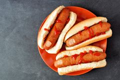 Halloween hot dog fingers on an orange plate over slate Stock Photo