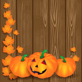 Halloween illustration with pumpkins and leaves on wooden backgr Royalty Free Stock Photos