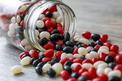 Halloween a inspiré le pot de dragées à la gelée de sucre rouges, blanches et noires se renversant sur une table en bois Un festi images stock