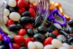 Halloween a inspiré le pot de dragées à la gelée de sucre rouges, blanches et noires se renversant sur une table en bois Un festi image stock