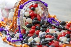 Halloween a inspiré le pot de dragées à la gelée de sucre rouges, blanches et noires se renversant sur une table en bois Un festi photos stock