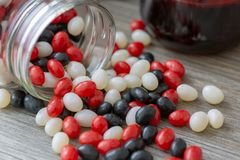 Halloween inspired jar of red, white and black jelly beans spilling out onto a wooden table. A perfect fall sweet treat. royalty free stock photography