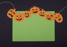 Creative card for invitation for Halloween with handmade paper square frame and yellow smiling scary pumpkins on a black paper, pl royalty free stock photos