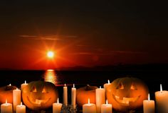 Halloween. Jack lantern, Orange pumpkins, candles, sunset, sun, sea, royalty free stock photo