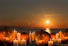 Halloween. Jack lantern, Orange pumpkins, candles, sunset sun sea royalty free stock images