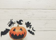 Halloween. jack lantern pumpkin with witch ghost bats and spider. Black decorations on white wooden background. simple cutouts for autumn holiday celebration Stock Photo