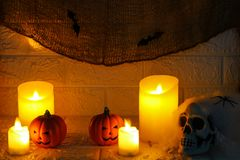 Halloween pumpkins, candles and horror skull on wall background Stock Images