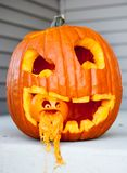 Halloween jack-o-lantern with another jack-o-lantern in its mouth with pumpkin flowing out of the little jack-o-lanterns mouth stock images