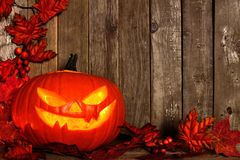 Halloween Jack o Lantern with an autumn leaves corner border on wood Royalty Free Stock Photos