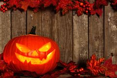 Halloween Jack o Lantern with an autumn leaves double border on wood Stock Photo