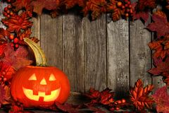 Halloween Jack o Lantern with an autumn leaves frame on wood Royalty Free Stock Photo