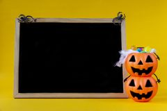 Halloween Jack o Lantern bucket and blank chalkboard on yellow b stock images