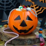 Halloween Jack o Lantern bucket overflowing with candy, spooky Halloween decorations on background, square format stock images