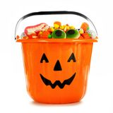 Halloween Jack-o-Lantern candy collector filled with candy over white Royalty Free Stock Image