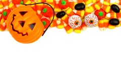 Halloween Jack o Lantern candy holder with candy top border. Halloween Jack o Lantern candy holder with top border of candy corn and other treats over white royalty free stock photo
