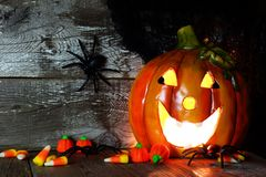 Halloween Jack o Lantern and candy, night scene against wood Stock Photography
